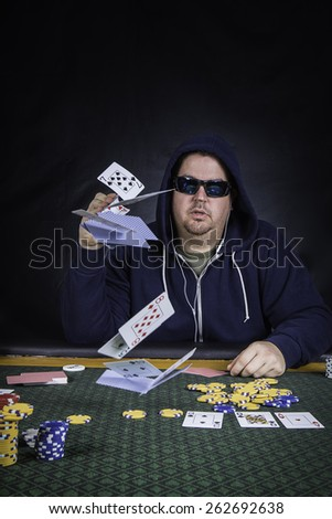 A man sitting at a poker table wearing a hoodie gambling and throwing his cards against a black background - stock photo