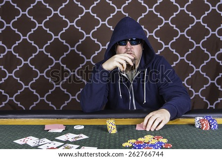 A man sitting at a poker table wearing a hoodie gambling playing cards against a brown background - stock photo