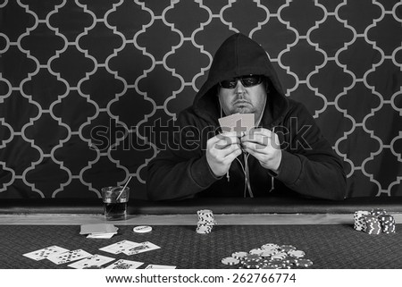 A man sitting at a poker table wearing a hoodie gambling playing cards in black and white - stock photo