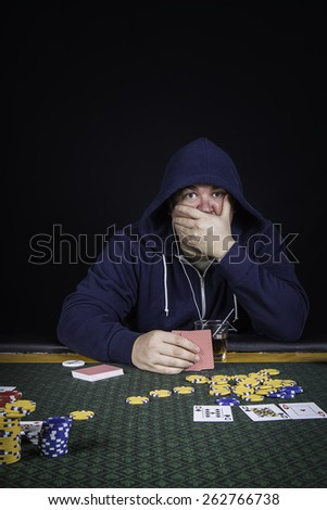 A man sitting at a poker table wearing a hoodie stressed gambling playing cards against a black background - stock photo
