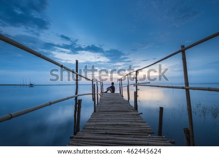 A man sitting at the end of the bridge at lake during sunset