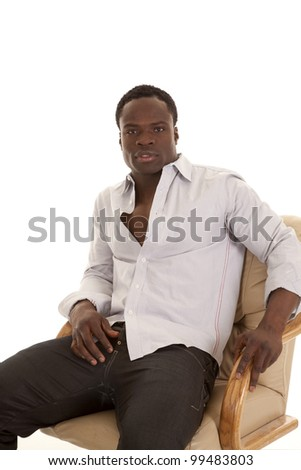 A man sitting in a chair looking stylish with a serious expression on his face.
