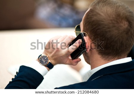 A man sitting in the cafe and calling by phone. He has a serious look, blue jacket, white shirt.