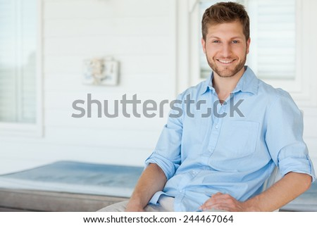A man sitting in the porch smiling looking straight ahead