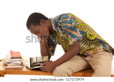 A man sitting on a wood bench with a stack of books looking and studying.