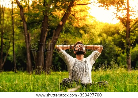 A man sitting on grass in the park and stretching with eyes closed and hands behind head. Concept of meditation, dreaming, wellbeing and healthy lifestyle - stock photo