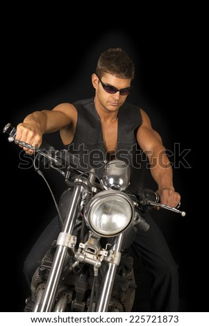 A man sitting on his motorcycle wearing his black vest and sunglasses.