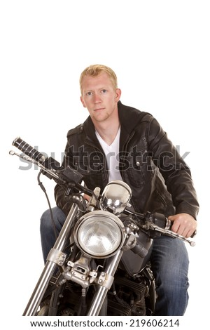 A man sitting on his motorcycle with a serious expression on his face. - stock photo
