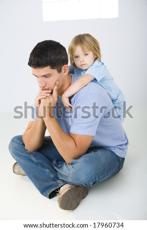 A man sitting on the floor with cross-legged and his daughter hugging him. A man looks like thoughtful.