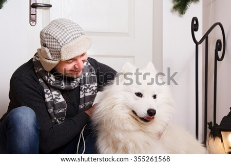 A man sitting on the porch with his dog. Friendship, four-legged friend. Winter Holidays, Christmas - stock photo