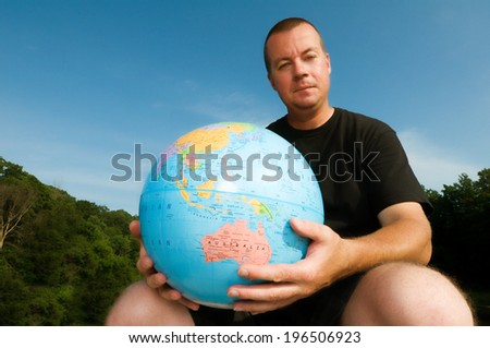 A man sitting outside, holding a large globe.