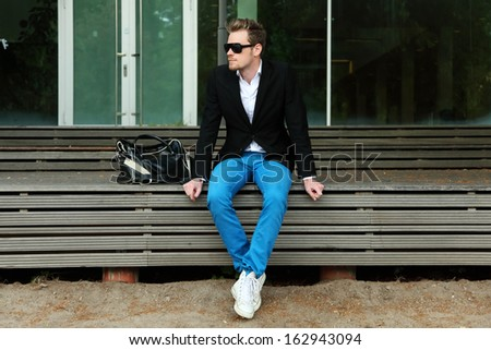 A man sitting outside wearing black sunglasses and a black jacket with blue jeans. - stock photo