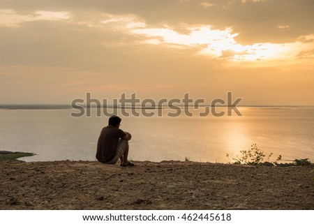 A man sitting seeing the sunset at lake