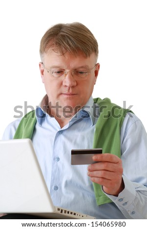 A man sitting with a laptop, holding a credit card - stock photo