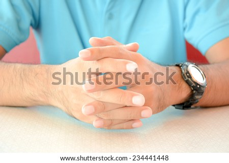 A man sitting with clasped hands on the table - stock photo