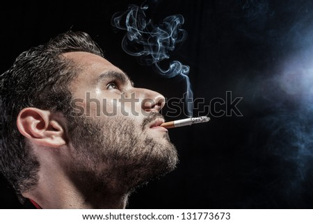 a man smoking a cigarette on a black background