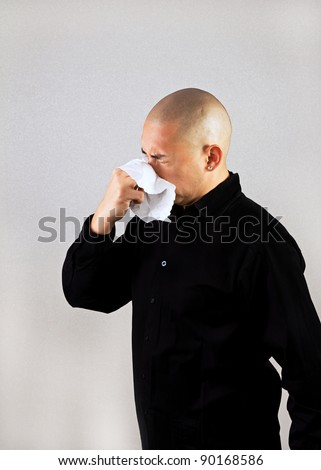 A man sneezing into a tissue - stock photo