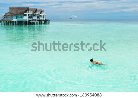A Man snorkeling in the Perfect Tropical Island, Maldives - stock photo