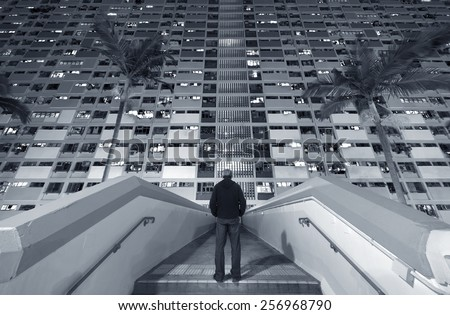 A man stand in front of a crowded residential building - stock photo