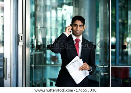 A man standing at the door on his phone.