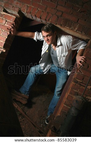 A man standing in an old brick opening - stock photo