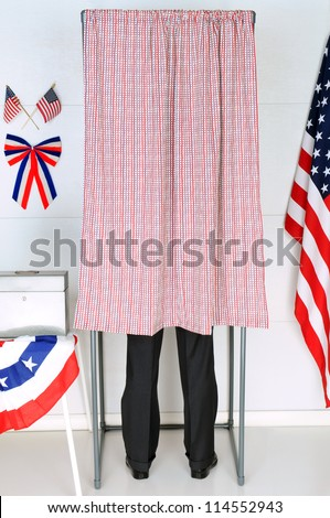 A man standing inside a voting booth at his local polling place. Vertical Format, man is unrecognizable.