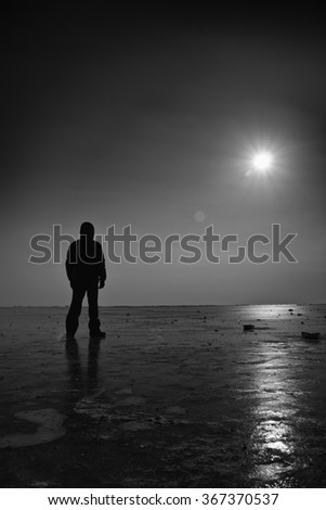 A man standing on a frozen sea. Abstract black and white photo.
