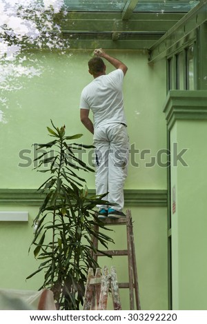 A man standing on a ladder and painting walls in green, shot through a window - stock photo