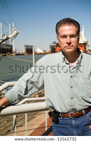 A man standing on a pier or deck with drilling rigs in the background. - stock photo