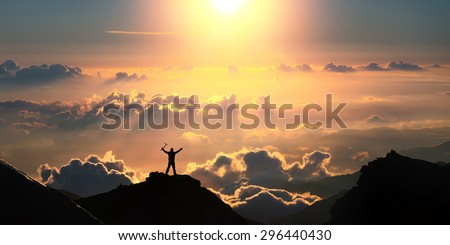 A man standing on the top of the mountain above the clouds with ice axe in his hands.  - stock photo