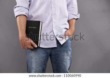 A man stands indoors with one hand holding a black bible and the other hand casually in his jeans pocket. - stock photo