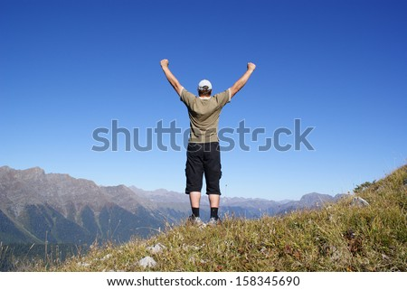 A man stands on a hillside with their hands up - stock photo