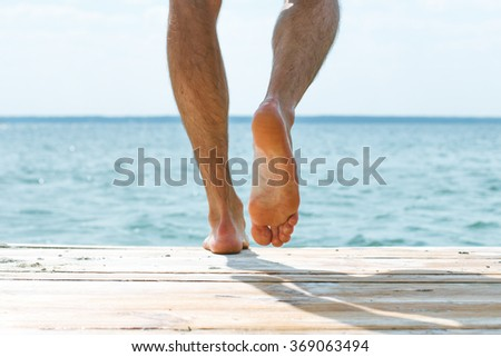 A man steps barefoot on the pier