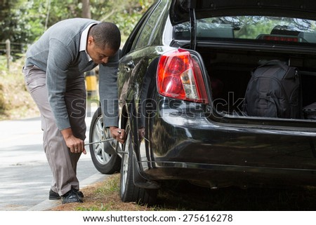 a man stranded on the road doing tire change - stock photo