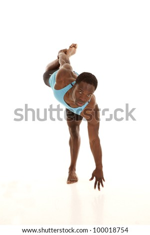 A man stretching his leg with a serious expression on his face showing off how flexible he is. - stock photo