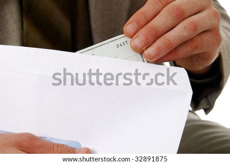 A man stuffing a check in an envelope