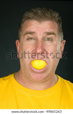 A man sucks on a lemon as he squints and puckers with the sour, tart flavor.