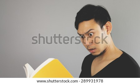 A man surprised the content in the yellow book. - stock photo