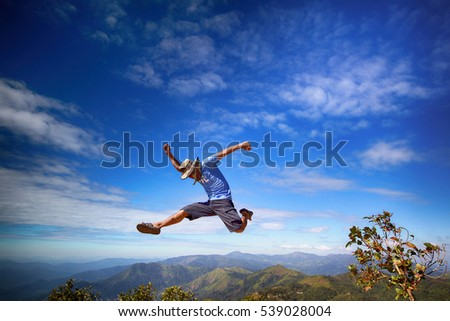 A man take high jump over mountain view / glad and jump up on blue sky background