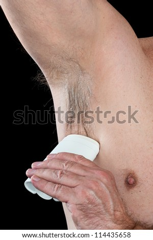 A man takes care of his hygiene by applying deodorant to his hairy armpit. - stock photo
