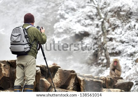 A man taking photos by professional digital camera in Snow Monkey, Japan - stock photo