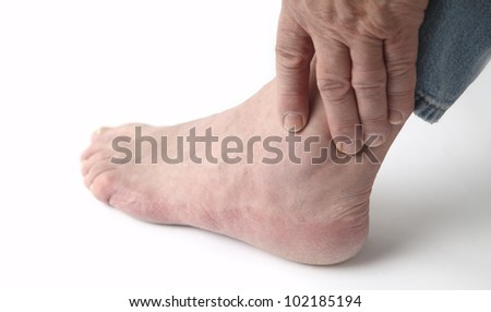 a man tends to his sore ankle - stock photo