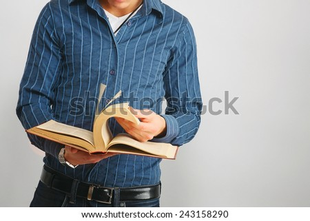 A man thumbing through a book, isolated on grey - stock photo