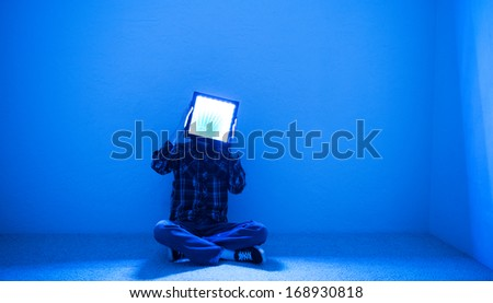 A man trapped in a small room with a square block with light coming out of it attached to his head. - stock photo