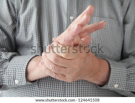 a man tries to restore feeling in his hand by squeezing - stock photo