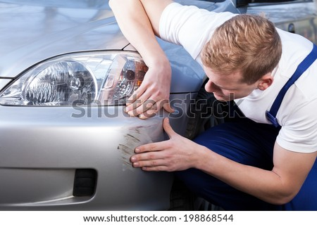 A man trying to fix a scratch on a car body - stock photo