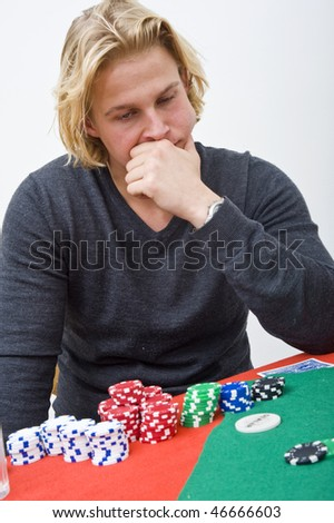 A man trying to make a decision on his strategy during a poker game - stock photo