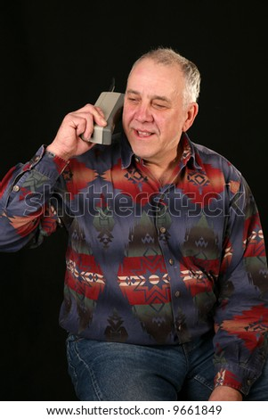 "a man uses a 1980s era cellular telephone also known as a ""brick phone"""