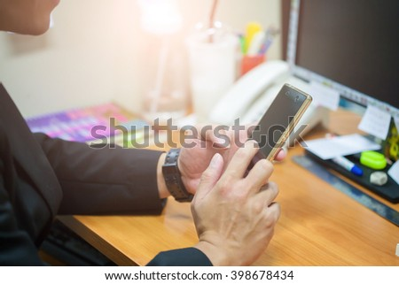 A man uses a smartphone. - stock photo