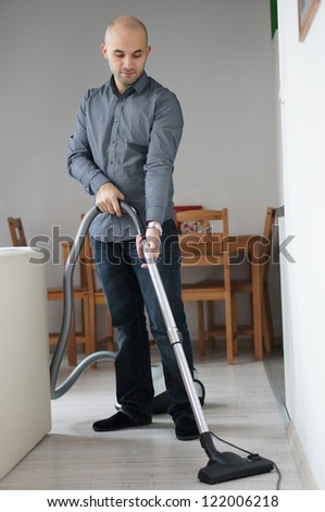A man using a vacuum cleaner - stock photo